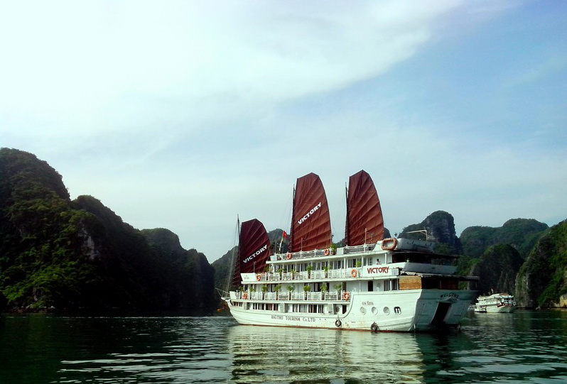 A cruise boat is dwarfed by one of the limestone karsts